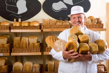 dorset: Portrait of baker in white uniform holding loaves of bread