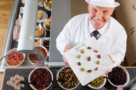 sales clerk: Sales clerk displaying specialty olives