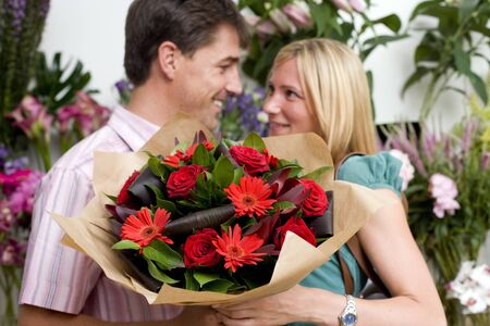 appreciating: Couple with bouquet of flowers in shop, smiling at each other LANG_EVOIMAGES