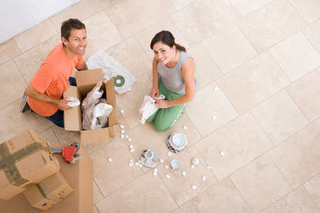 unpacking: Young couple unpacking boxes, smiling, portrait, elevated view LANG_EVOIMAGES