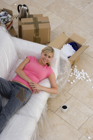 packing material: Woman on sofa in plastic cover by boxes, smiling, portrait