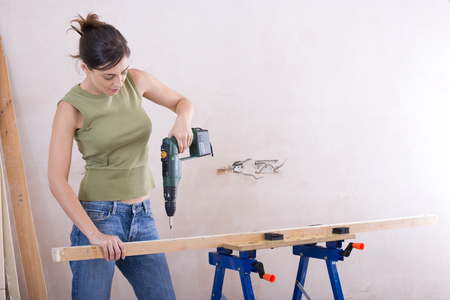 sawhorse: Woman drilling wood on sawhorse LANG_EVOIMAGES
