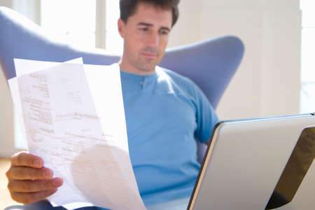 paying bills online: Man with paperwork in armchair, low angle view