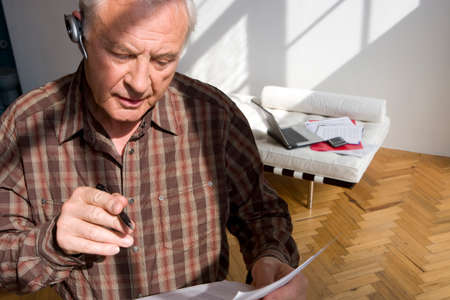 pagando: Hombre mayor con el papeleo y manos libres dispositivo LANG_EVOIMAGES