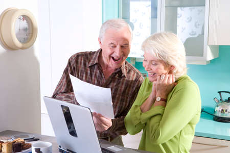 paying bills online: Senior couple in kitchen with laptop computer and paperwork