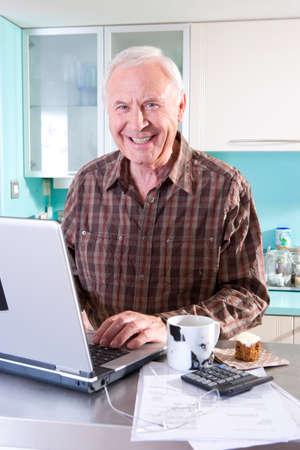 paying bills online: Senior man with laptop computer in kitchen, portrait