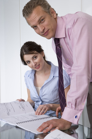 Businesswoman and colleague with paperwork, portrait