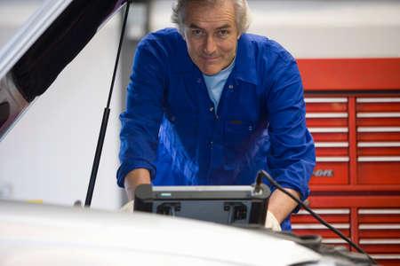 auto mechanic: Mechanic with electronic diagnostics machine, portrait