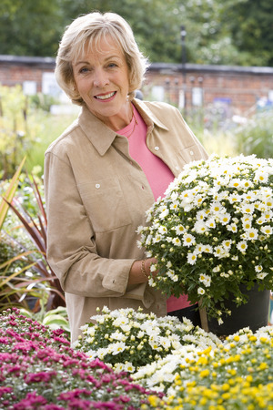 tuincentrum: Woman with plant in garden center, smiling, portrait