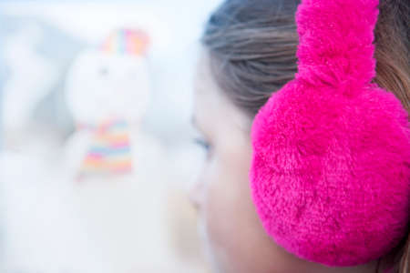 earmuff: Close up of girl wearing bright pink earmuffs