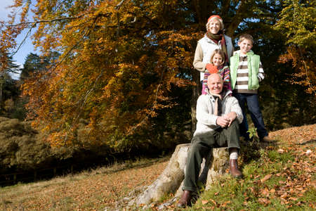 grandkids: Portrait of grandparents and grandkids in grass with autumn leaves
