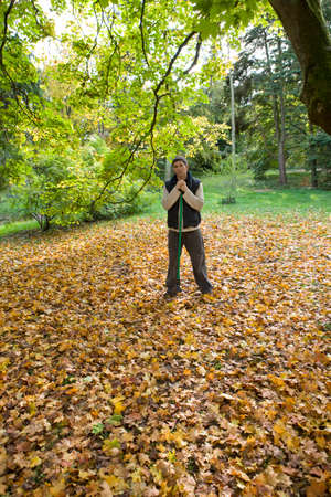 tetbury: Portrait of man with rake standing in autumn leaves