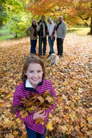 tetbury: Portrait of girl holding autumn leaves with family in background