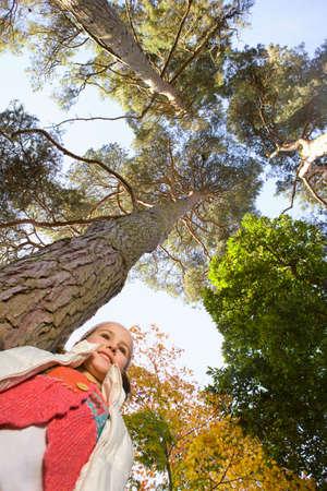tall tree: Girl standing under tall tree