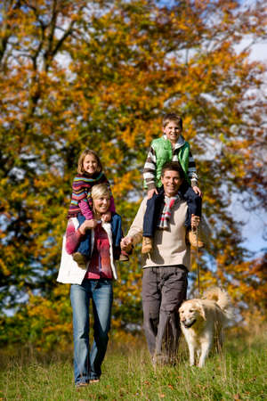 tetbury: Portrait of family and dog walking through field LANG_EVOIMAGES