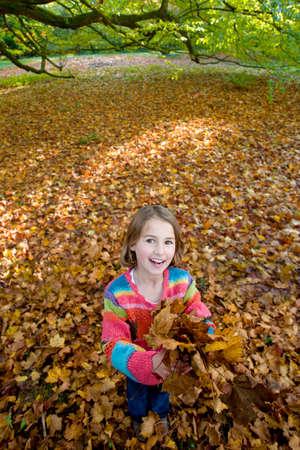 tetbury: Portrait of girl holding autumn leaves
