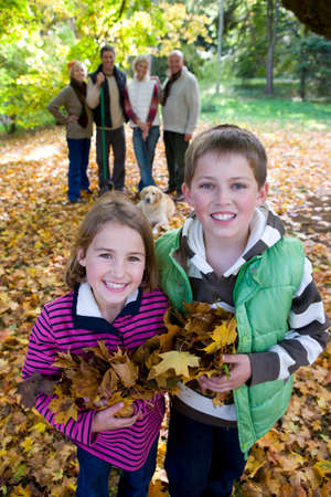 tetbury: Portrait of boy and girl holding autumn leaves with family in background LANG_EVOIMAGES
