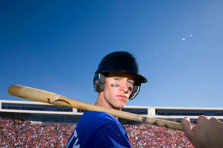 baseball crowd: Portrait of baseball player holding bat with crowd in background LANG_EVOIMAGES