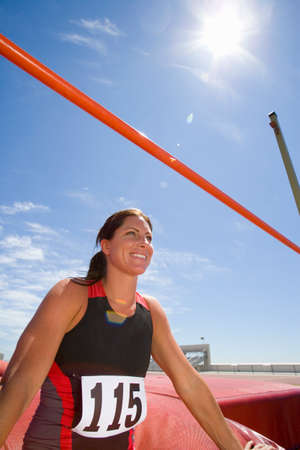 angle bar: Young female athlete by bar, low angle view (lens flare) LANG_EVOIMAGES