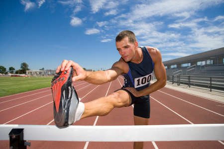hamstrings: Male athlete stretching hamstrings, foot on hurdle, low angle view LANG_EVOIMAGES
