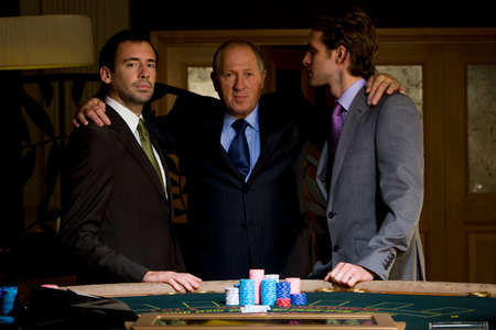 high stakes: Mature man with arms around young men by poker table, portrait