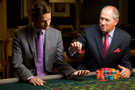 Mature man with giving young man gambling chip at roulette table