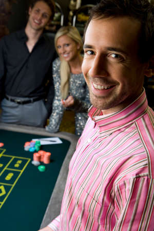 roulette table: Young man by friends gambling at roulette table, smiling, portrait, close-up