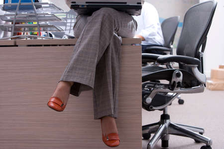 low section: Businesswoman on desk with laptop computer, low section LANG_EVOIMAGES