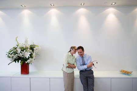 confiding: Businessman and woman with headsets in conversation, smiling LANG_EVOIMAGES