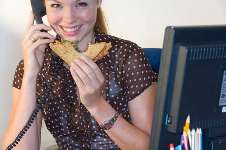 unprofessional: Woman on telephone at desk with sandwich, smiling, portrait LANG_EVOIMAGES