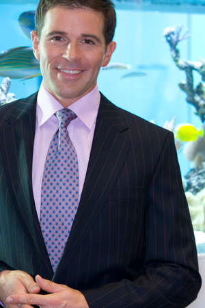 fish tank: Businessman by fish tank, smiling, portrait