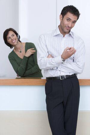 loitering: Businessman by receptionist, smiling, portrait LANG_EVOIMAGES