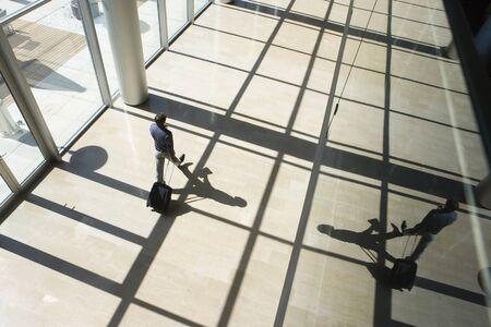 wheeling: Businessman wheeling luggage in lobby