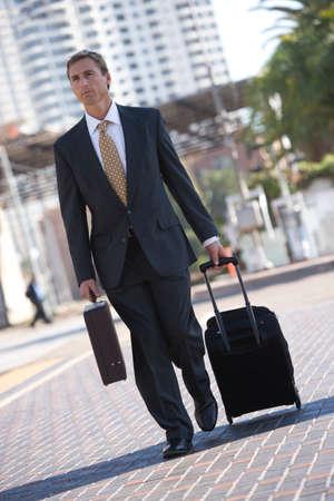 wheeling: Businessman wheeling luggage in urban setting