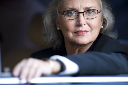 head close up: Serious senior businesswoman with eyeglasses