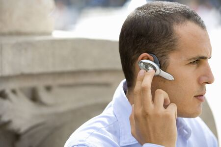 handsfree phone: Businessman using hands-free cell phone headset LANG_EVOIMAGES