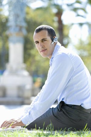 handsfree device: Businessman using hands-free cell phone headset LANG_EVOIMAGES