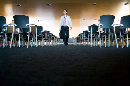 lecture hall: Businessman with briefcase leaving empty lecture hall