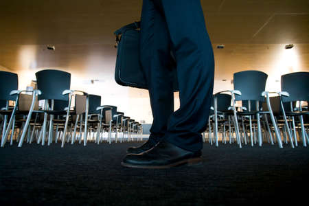 lecture hall: Businessman holding briefcase in empty lecture hall