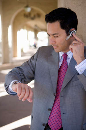handsfree: Businessman using hands-free cell phone headset LANG_EVOIMAGES