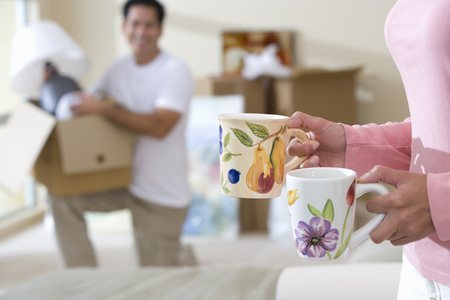 Woman carrying coffee mugs