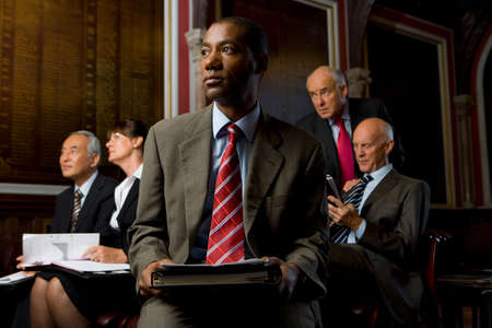 professionalism: Businessman with paperwork, colleagues in background