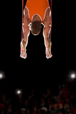 gymnastique: Homme gymnaste effectuer sur les anneaux de gymnastique, vue arri�re