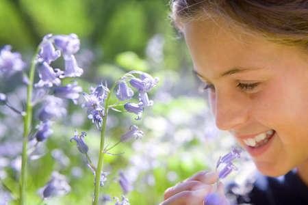 bluebell: Girl smelling bluebell flower LANG_EVOIMAGES