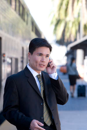 business: Businessman talking on cell phone at train station