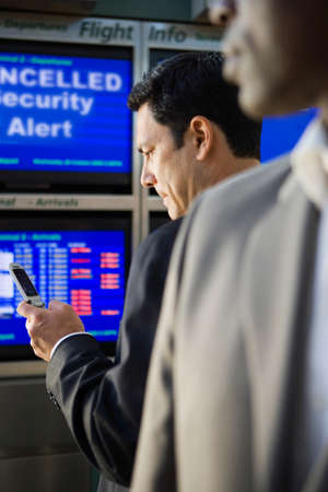 north western european descent: Businessman using cell phone in airport