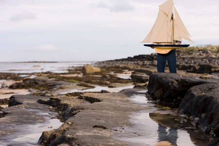 western european: Man holding model sailboat