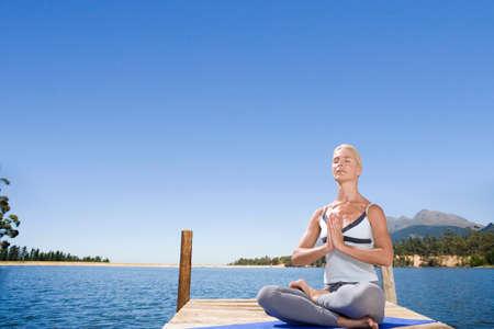 spiritualism: Woman meditating on lake dock LANG_EVOIMAGES