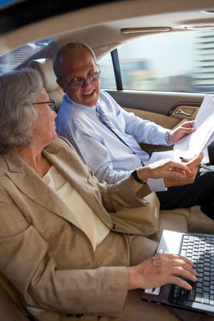 conferring: Businesswoman and businessman riding in town car