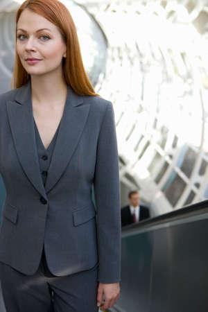 western european: Businesswoman riding escalator LANG_EVOIMAGES